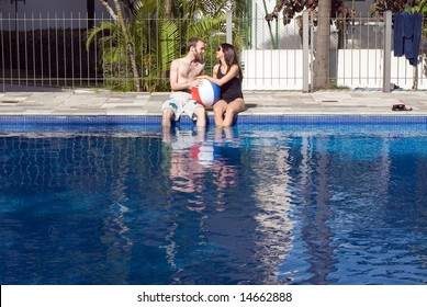 A man and a woman are relaxing together beside a pool.  They are looking at each other and dipping their legs in the water.  They are holding a beach-ball, Horizontally framed photo.