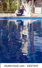 A man and a woman are relaxing together beside a pool.  They are leaning against each other.  The man is looking away from the camera and the woman is looking at it.  Vertically framed photo.