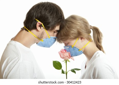 Man and woman   in  respirators smelling rose  against white background