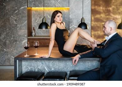 Ein Mann und eine Frau in einem Restaurant, Loft. Ein Mädchen in einem schwarzen Kleid mit einer Scheibe sitzt auf einem Tisch mit einem Glatzköpfchen in einem Anzug mit einer Gläser Wein, ein Mann hält ein Mädchen das Bein. Valentinstag