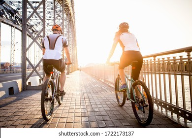 a man and a woman ride a Bicycle towards the setting sun