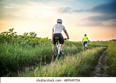 Man and woman riding bicycles in a field at sunset in the fall, summer. The girl and the guy on the bike involved in cycling. Walk on bicycles outdoors.
