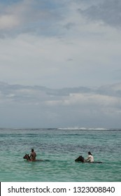 A man and a woman riding a horse into the sea, Mauritius