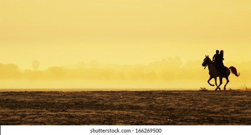 Man and woman riding a horse at sunrise