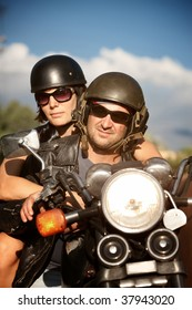 Man and Woman riding motorcycle against Blue Sky