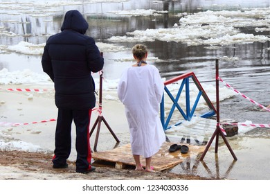 A man and woman in ritual white clothing standing by the swims in cold water outdoor - religion,Faith, Christianity, baptism, winter bathing ritual in the cross ice hole on the river among the ice flo