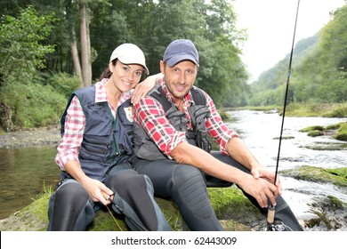 Man and woman in river fly fishing