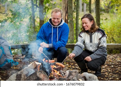 Man and woman roasting on campfire in forest on shore of lake, making a fire, grilling. Happy couple exploring Finland. Scandinavian landscape.