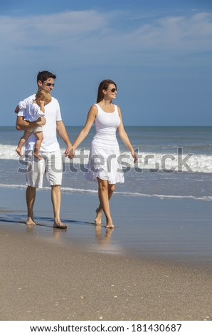 c61d428f1af2 Man and woman romantic couple in white clothes holding hands walking  holding baby child on a
