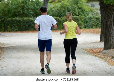 A man and a woman are running around in the park. View from the back