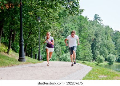 a man and a woman running in the park race