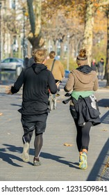 Man and woman are running through the park in autumn in cologne germany 2018.