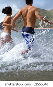 A man and a woman running in the water seen from the back
