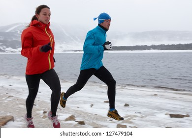 Man and woman running in winter