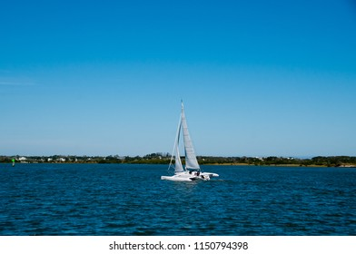 man and woman sailing a white trimaran multihull sailboat on the intracoastal waterway in Florida, USA