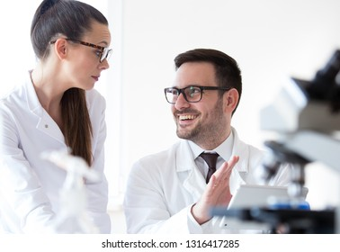 Man and woman scientists analyzing data from microscope test