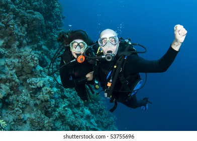man and woman scuba dive together and have fun
