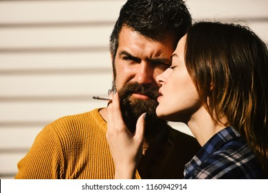 Man and woman with serious faces on white stripy background, defocused. Girl and bearded guy hug and hold cigarette. Couple in love smokes together. Smoking and habit relationship concept