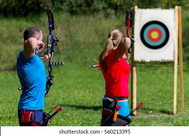 Man and woman are shooting with bows. Practicing Archery