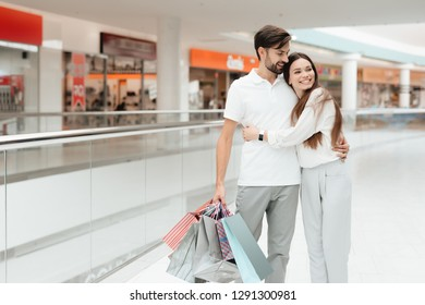 Man and woman with shopping bags in shopping mall. Couple is hugging.