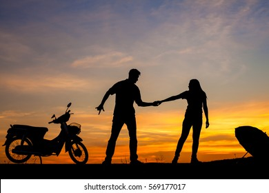 Man and woman showing the love in evening sunset silhouette.