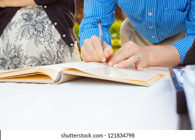 A man and a woman sign a wedding guestbook with a pen.