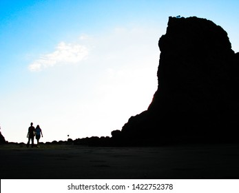 A man and a woman (silhouettes) walk on a rocky beach at twilight.