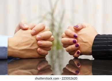 Man and woman sits at a desk with hands clasped. marital problems, conflicts and stubborn concept