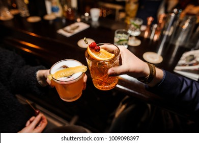man and a woman are sitting at a bar counter and clinking glasses of alcoholic cocktails- sour mix and negroni with orange and cherry