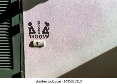 Man and woman sitting in the bathroom icon at the wall, sign symbol