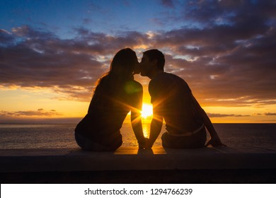 Man and woman sitting by the sea kiss at sunset at Meloneras beach walk, Gran Canaria. Couple silhouette enjoying colorful twilight. Valentines Day, honeymoon romantic date concepts