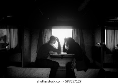 A man and a woman are sitting near a window in a train. B/w photo
