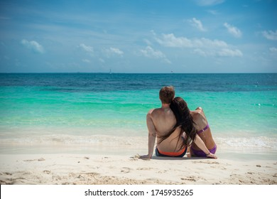 A man and a woman are sitting on the seashore and looking at the horizon.