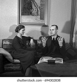 Man and woman sitting on sofa having a conversation in sign language