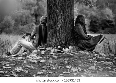 Man and woman sitting in park after quarrel