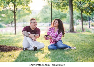 Man and woman sitting at park looking at phone horizontal