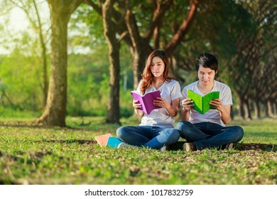 man and woman sitting and reading a book in the park