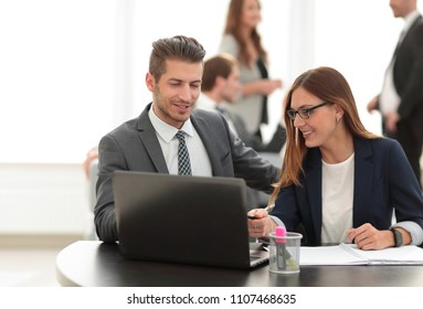 man and woman sitting at table in co-working office