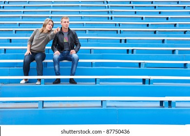 Man and woman sitting together on empty sports tribune along