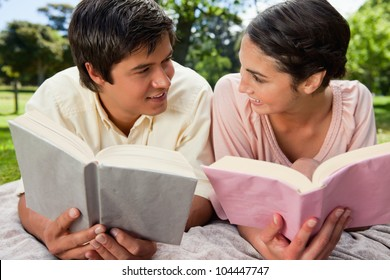 Man and a woman smiling at each other while reading books as they lie prone on a grey blanket in the grass