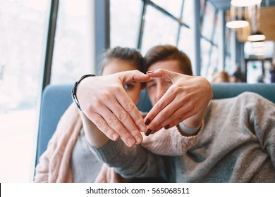 man and woman smiling with hands depict the heart. Two people in cafe communicate, laughing and enjoying the time spending with each other. Couple  on a date. Love story and Valentines Day concept