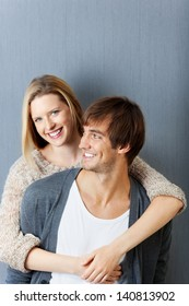 man and woman smiling and hugging in front of grey wall