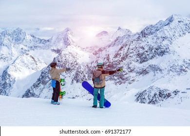 Man and Woman - snowboarders staying on snow slope planning the rout of ride down in mountain landscape