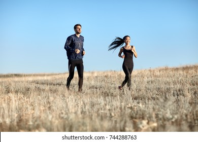 Man and woman in sportswear running in field. Two young athletic people engaged in sports. Fitness girl and guy running in countryside on sunny day. Healthy lifestyle, motivation, team concept