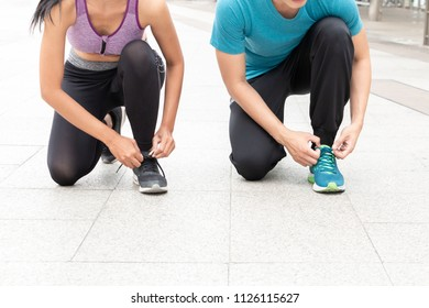 Man and woman in sportswear tying shoelaces of a sneakers on floor tile background. Man and woman sitting on floor and knotting lace on a running shoe.