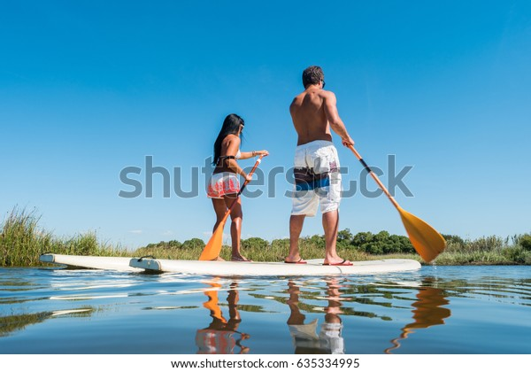 Man and woman stand up paddleboarding on lake. Young couple are doing watersport on lake. Male and female tourists are in swimwear during summer vacation.