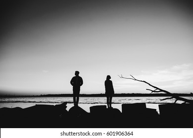 Man and woman stand separately on lake shore