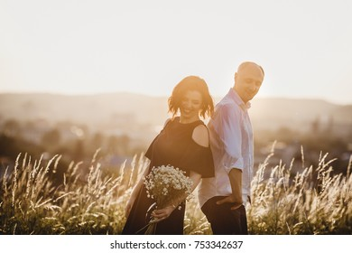 Man and woman stand side by side on the summer field