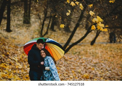 Man and woman stand under colorful umbrella in the park with golden fallen leaves
