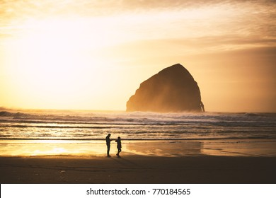 Man and woman standing in front of Haystack Rock in Cape Kiwanda State Park. Pacific City, Oregon, USA.